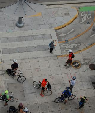 Aerial view of a sidewalk showing bike lane markings and pedestrian markings, with several cyclists and pedestrians moving through the space.