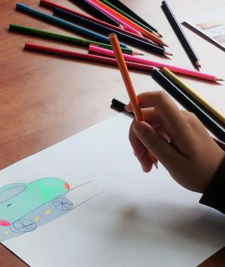 Close-up of a tabletop with a child's hand holding a colored pencil. On a piece of paper is a turquoise drawing of a car on a street. More colored pencils are in the background.