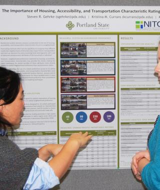 Two women stand in front of a research poster discussing neighborhood housing, accessibility, and transportation