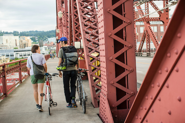 Two people walking their bikes over the Broadway Bridge