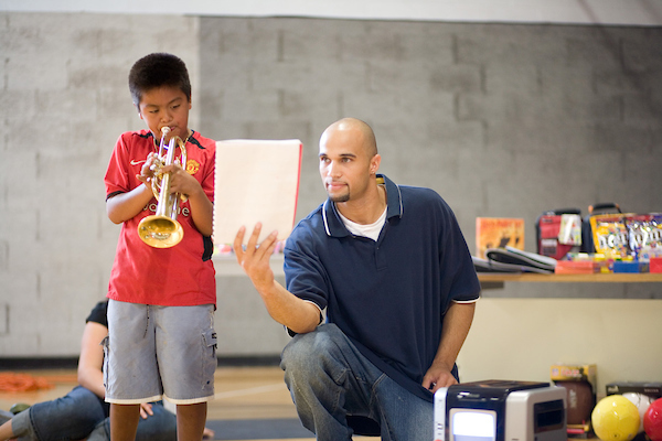 Student with child playing an instrument.