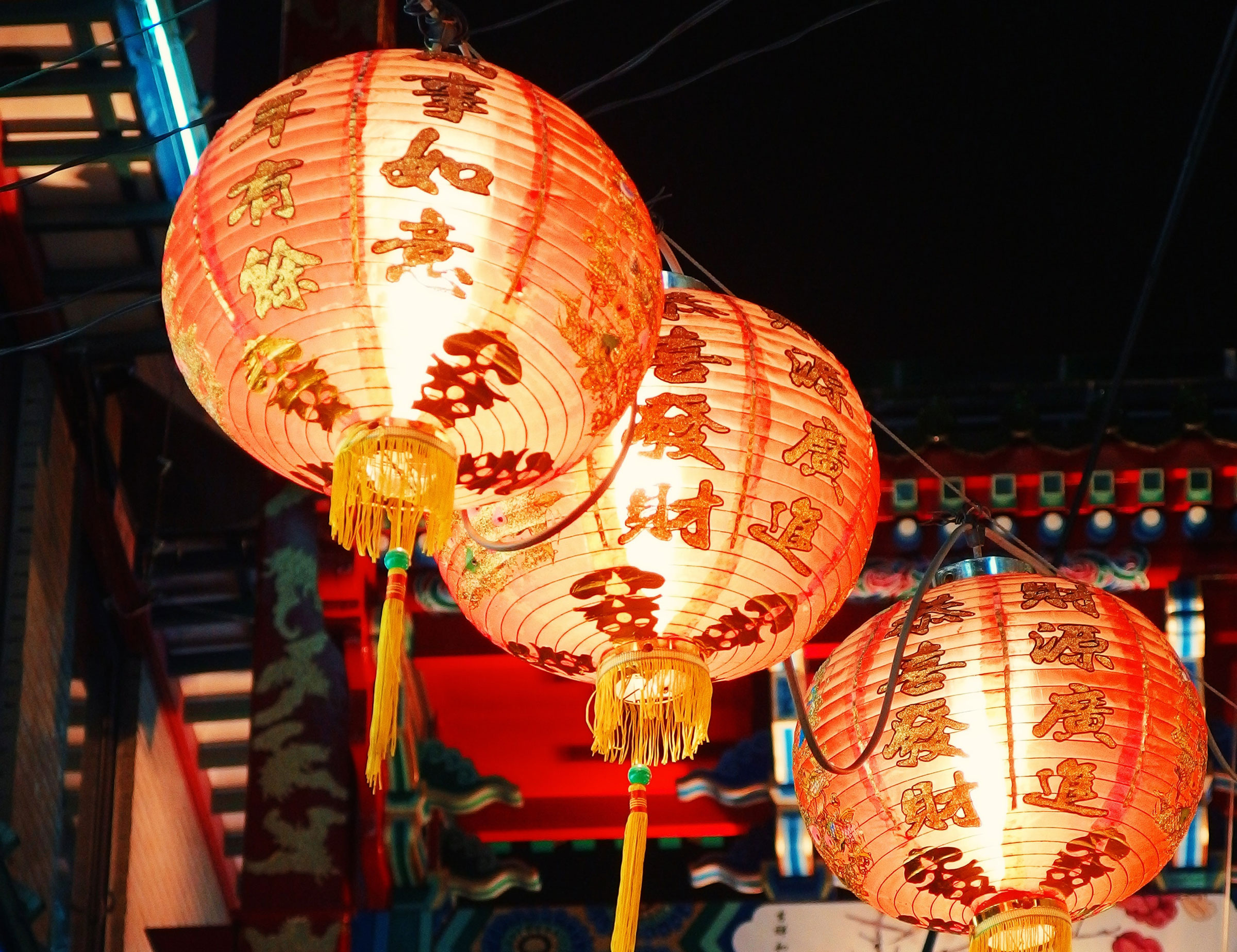 three lit chinese hanging lanterns