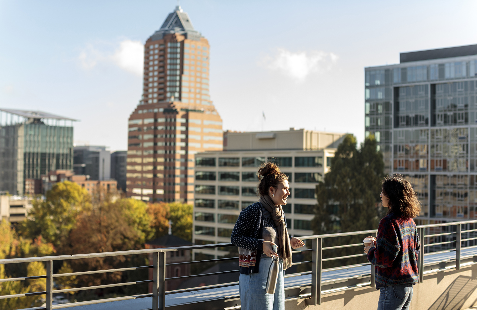 Two PSU Urban Studies students talking on a rooftop terrace