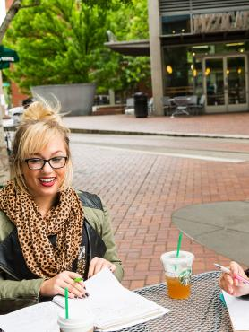 two Portland State University public policy students studying by a coffee shop