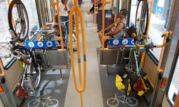 Riders sit on a TriMet MAX train; in a foreground a bicycle hangs from the train's bike hooks.