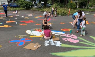 Children paint designs on the street near the school