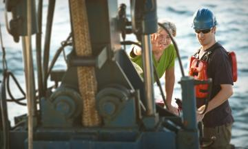 A man and a woman inspect machinery on a boat