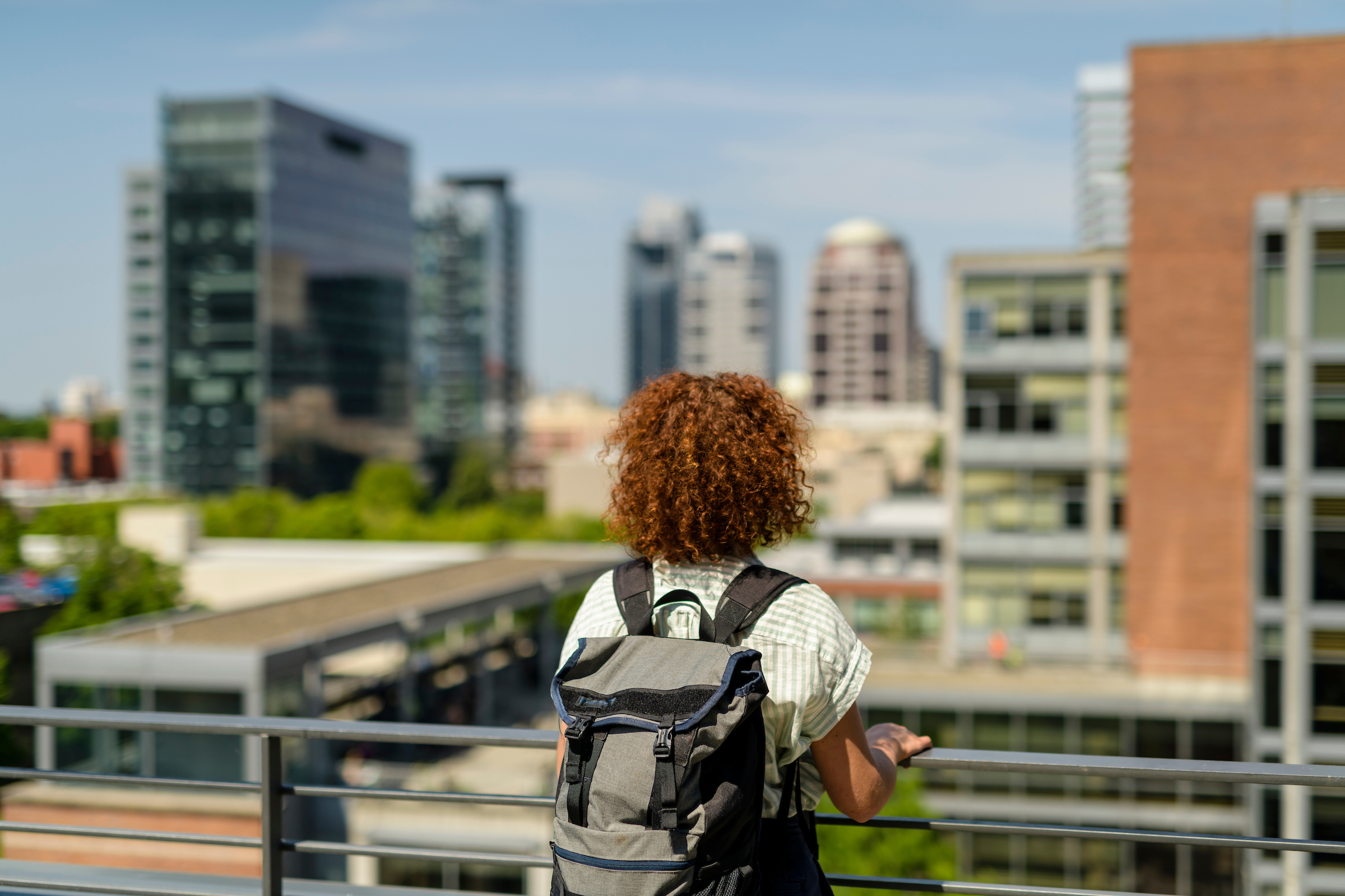 Back of woman with backpack looking at city