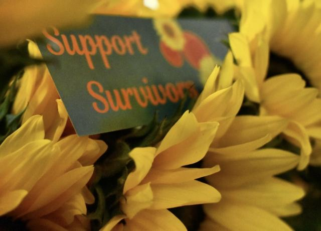 "A teal bookmark with orange text reading ""Support Survivors"" rests in between a bouquet of yellow sunflowers"