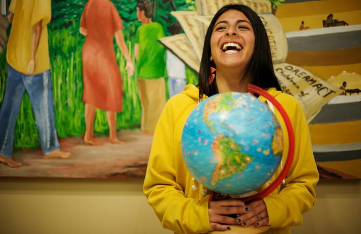 Student laughing while holding a globe